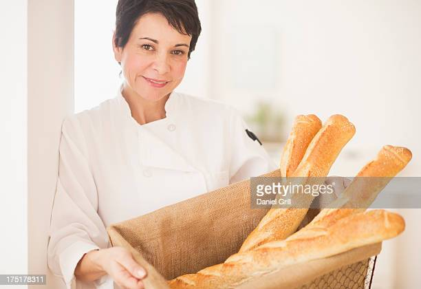 USA, New Jersey, Jersey City, Portrait of mature woman holding basket with baguettes