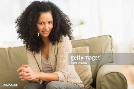 USA, New Jersey, Jersey City, Portrait of mid adult woman sitting on sofa : Stock Photo