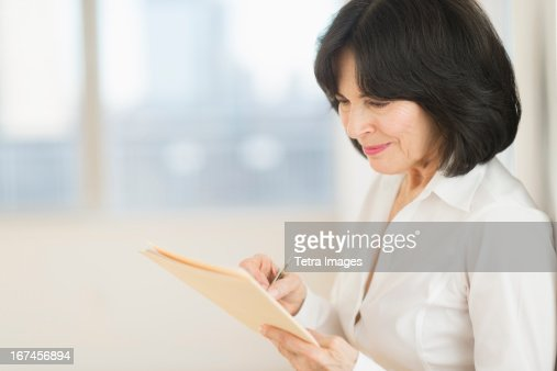 USA, New Jersey, Jersey City, Portrait of senior businesswoman writing : Stock Photo