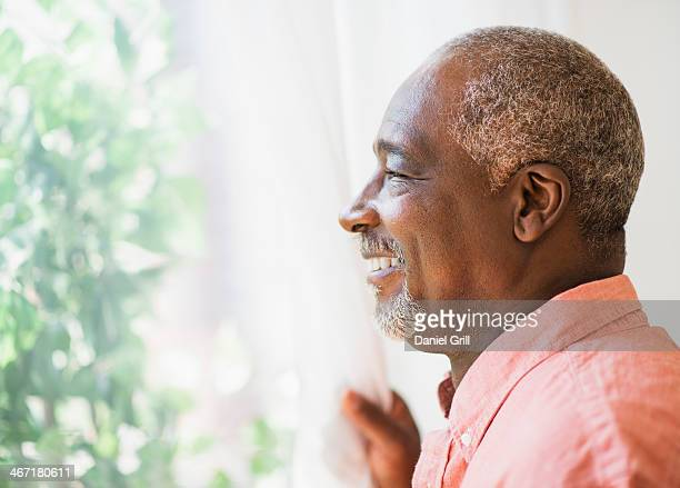 USA, New Jersey, Jersey City, Portrait of smiling man looking through window