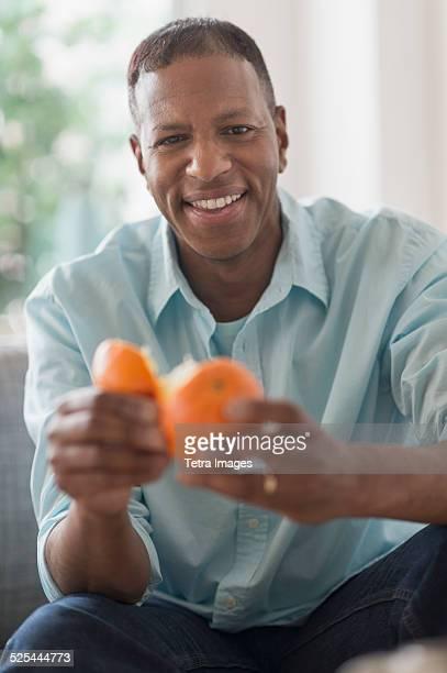 USA, New Jersey, Jersey City, Portrait of smiling man peeling orange fruit