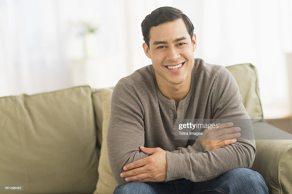 USA, New Jersey, Jersey City, Portrait of smiling man sitting on sofa : Stock Photo