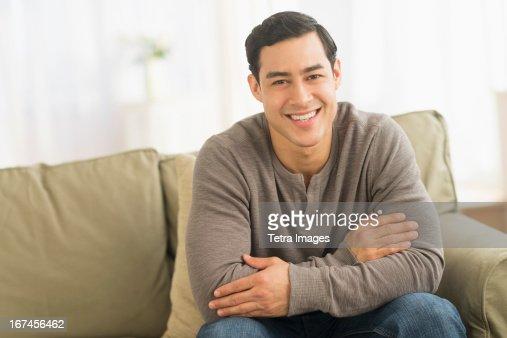 USA, New Jersey, Jersey City, Portrait of smiling man sitting on sofa : Stock Photo