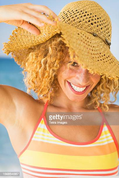 USA, New Jersey, Jersey City, Portrait of smiling young woman in sun hat
