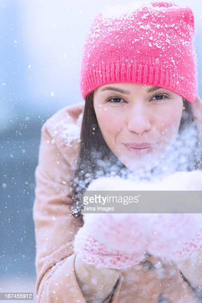 USA, New Jersey, Jersey City, Portrait of woman blowing snow from hands