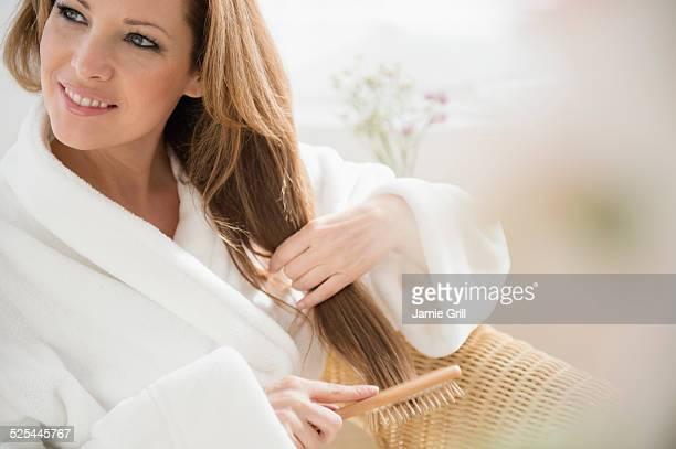 USA, New Jersey, Jersey City, Portrait of woman brushing hair