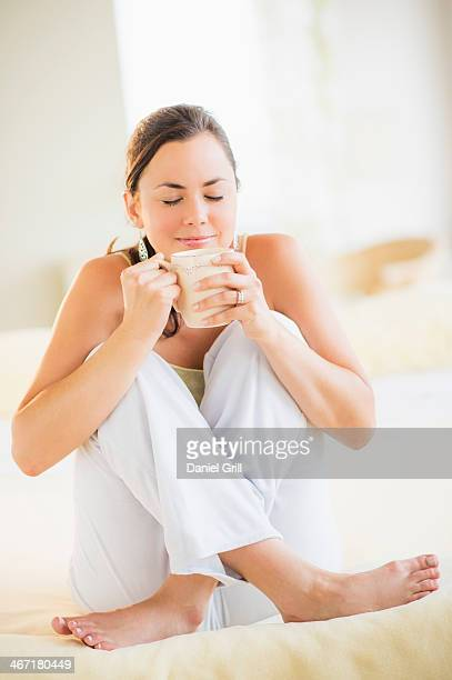 USA, New Jersey, Jersey City, Portrait of woman enjoying tea in bed
