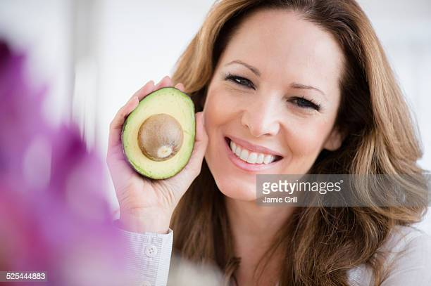 USA, New Jersey, Jersey City, Portrait of woman holding avocado
