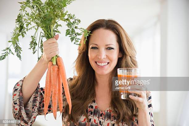 USA, New Jersey, Jersey City, Portrait of woman holding carrots and carrot juice
