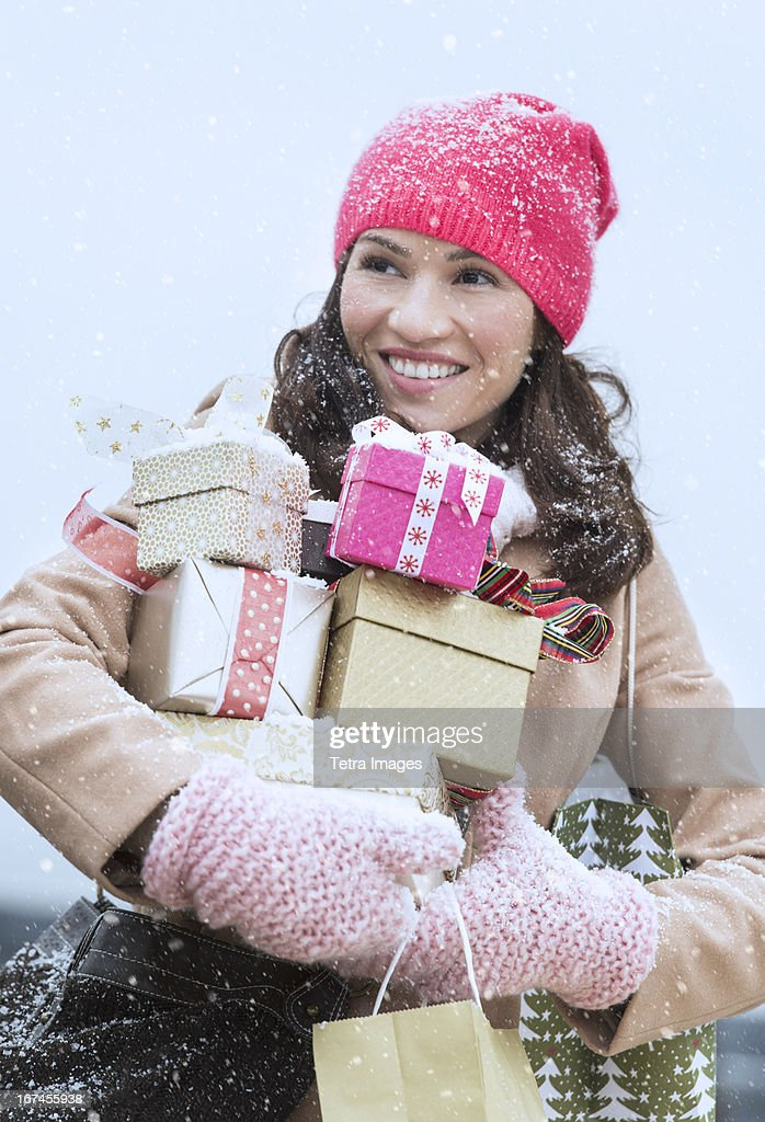USA, New Jersey, Jersey City, Portrait of woman in winter clothes carrying presents : Stock Photo