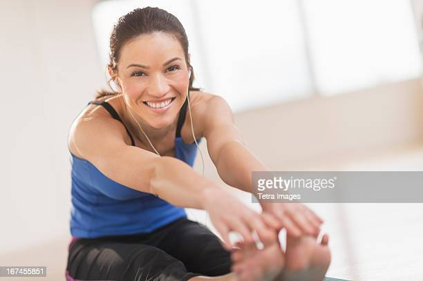 USA, New Jersey, Jersey City, Portrait of woman stretching in gym