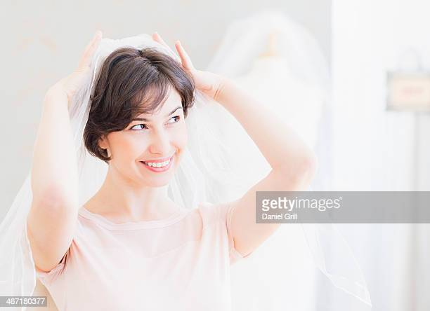 USA, New Jersey, Jersey City, Portrait of woman trying on wedding veil