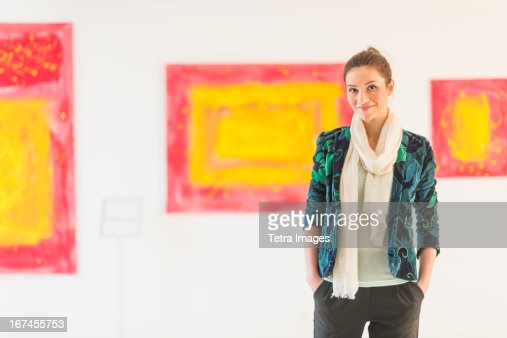 USA, New Jersey, Jersey City, Portrait of woman with paintings in museum