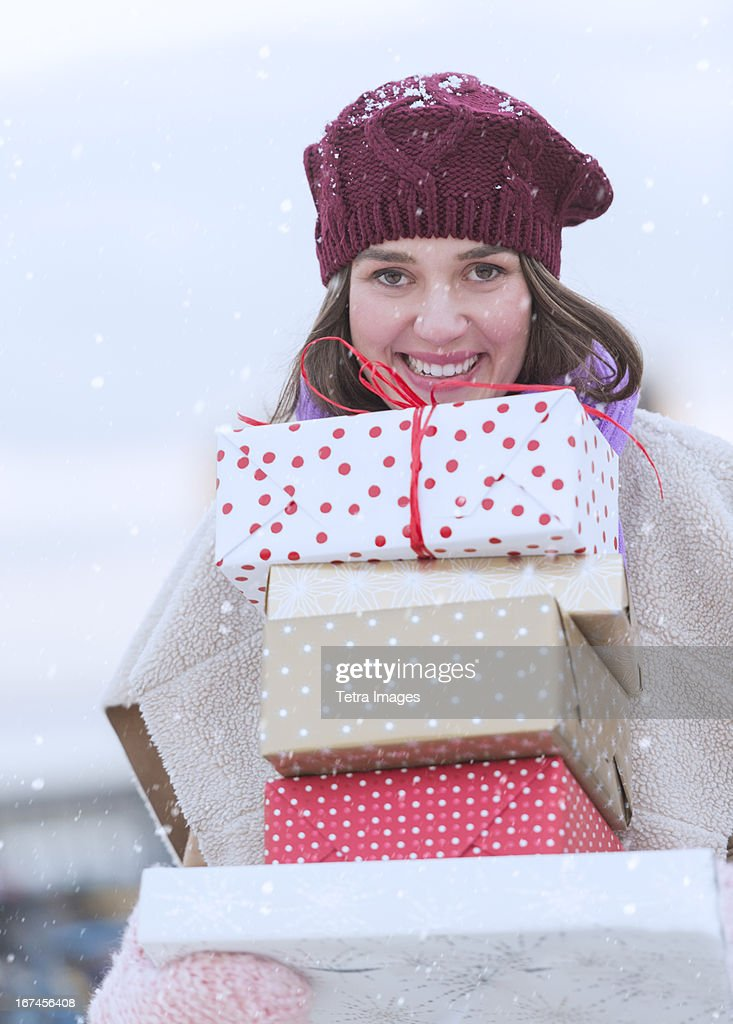 USA, New Jersey, Jersey City, Portrait of young woman carrying stack of Christmas presents : Stock Photo