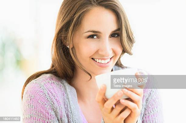 USA, New Jersey, Jersey City, Portrait of young woman drinking tea