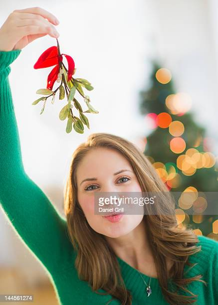 USA, New Jersey, Jersey City, Portrait of young woman holding mistletoe stem over head