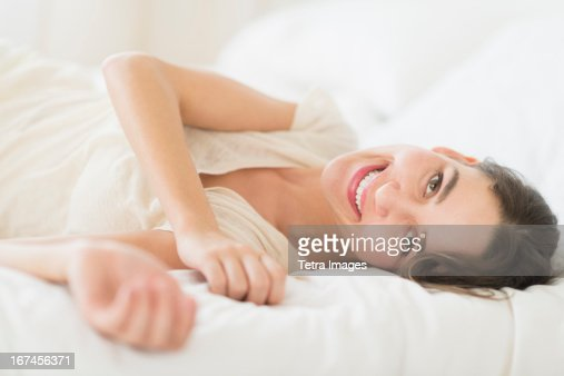 USA, New Jersey, Jersey City, Portrait of young woman lying in bed : Stock Photo