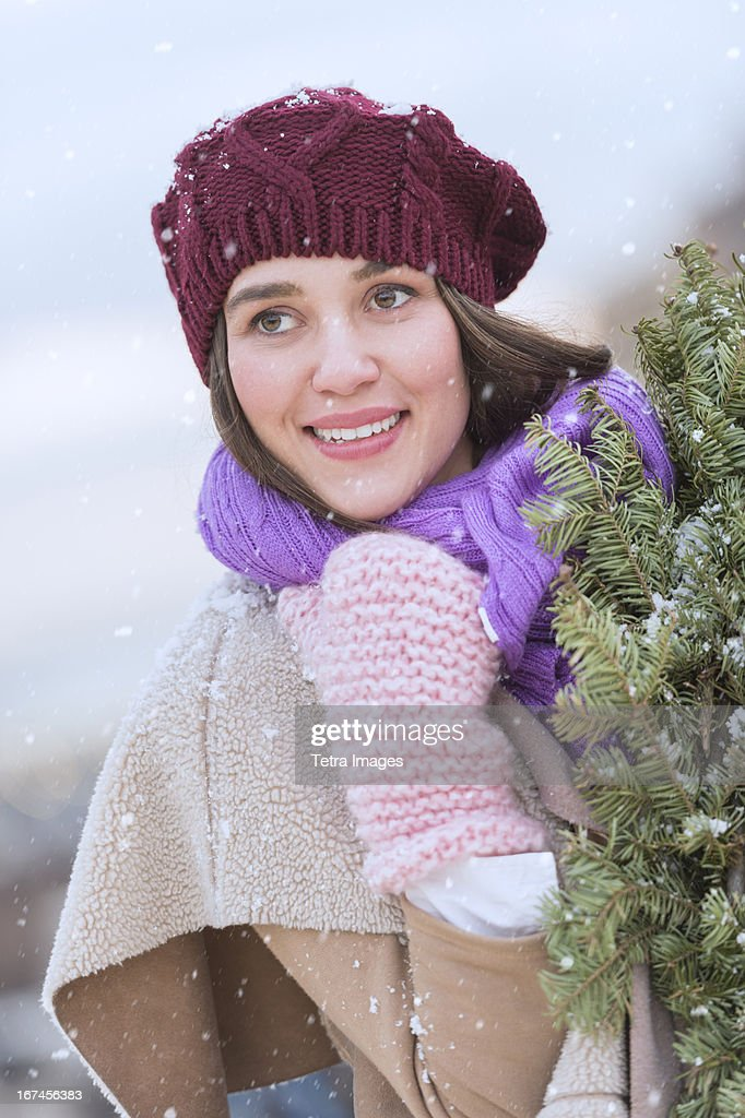USA, New Jersey, Jersey City, Portrait of young woman wearing knit hat, gloves and scarf an carrying fir wreath : Stock Photo