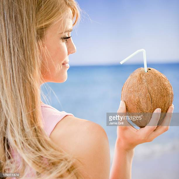 USA, New Jersey, Jersey City, Profile of woman holding coconut with straw