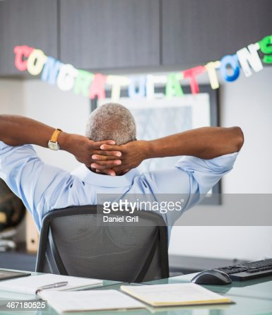 USA, New Jersey, Jersey City, Rear view of man in office, congratulations sign in background