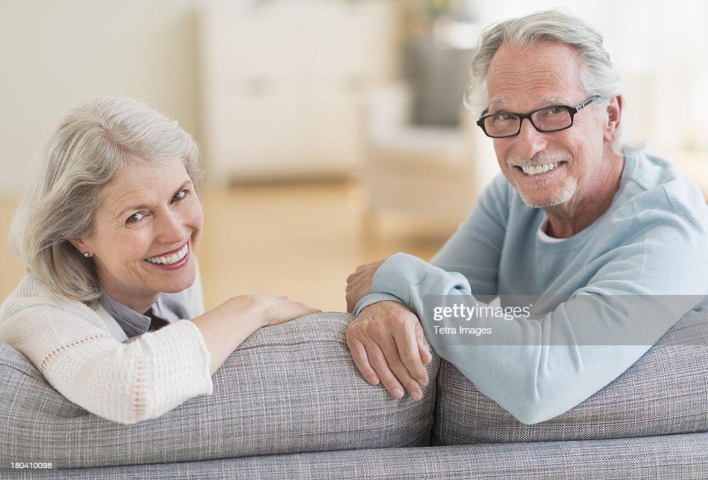 USA, New Jersey, Jersey City, Senior couple sitting on sofa : Stock Photo