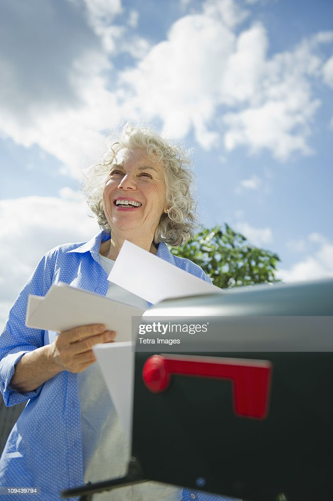 USA, New Jersey, Jersey City, Senior woman checking mail at mailbox : Stock Photo