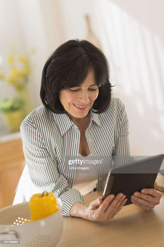 USA, New Jersey, Jersey City, Senior woman holding digital tablet in kitchen : Stock Photo
