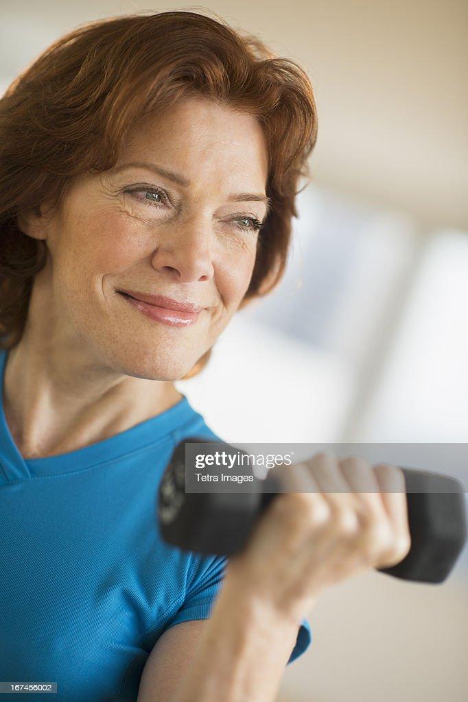 USA, New Jersey, Jersey City, Senior woman lifting weights : Stock Photo