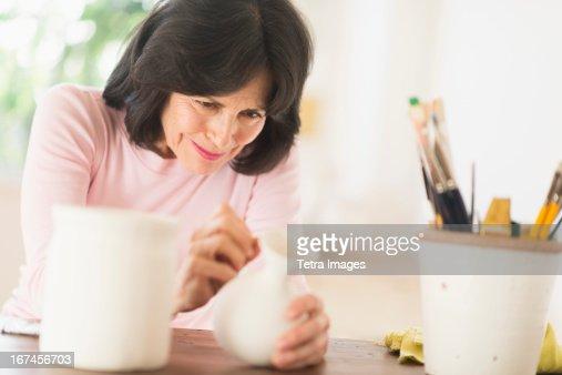 USA, New Jersey, Jersey City, Senior woman painting handmade pottery : Stock Photo