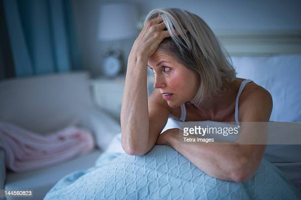 USA, New Jersey, Jersey City, Senior woman sitting in bed and suffering from insomnia