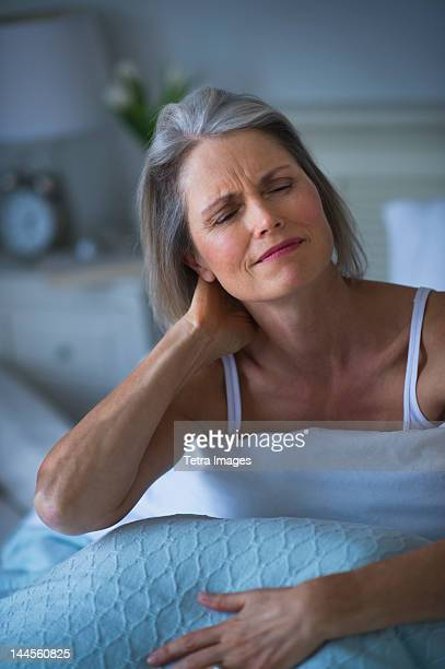 USA, New Jersey, Jersey City, Senior woman sitting in bed and suffering from necklace