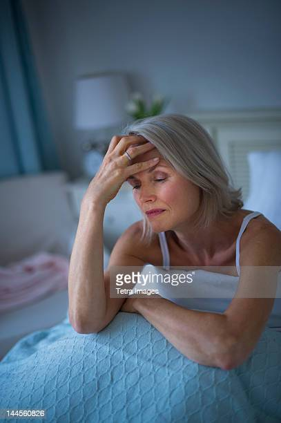 USA, New Jersey, Jersey City, Senior woman sitting in bed and suffering from headache
