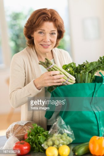 USA, New Jersey, Jersey City, Senior woman with groceries in kitchen : Stock Photo