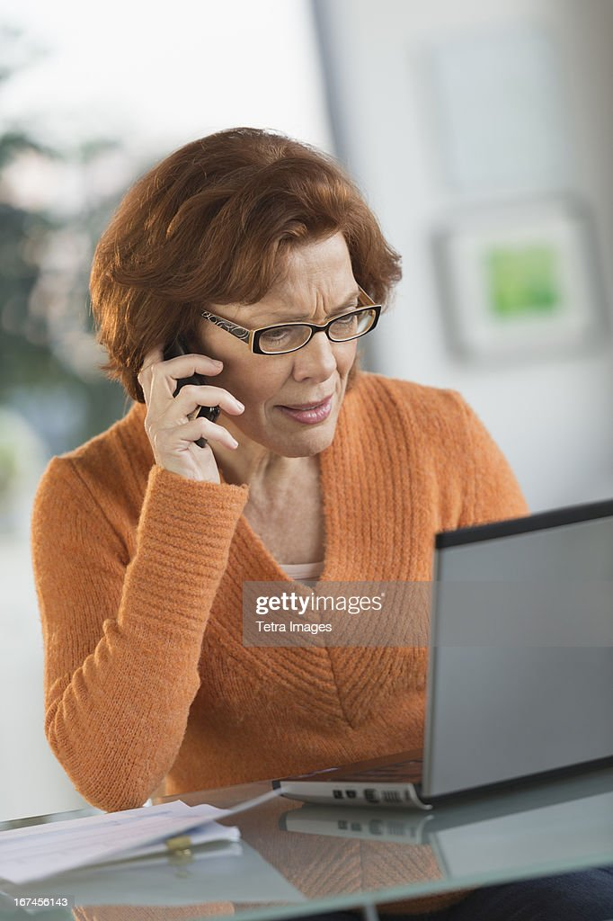 USA, New Jersey, Jersey City, Senior woman working on laptop and talking on cell phone : Stock Photo