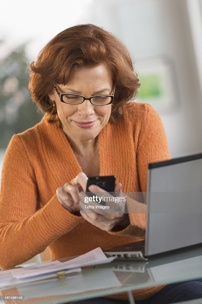 USA, New Jersey, Jersey City, Senior woman working on laptop and text messaging : Stock Photo