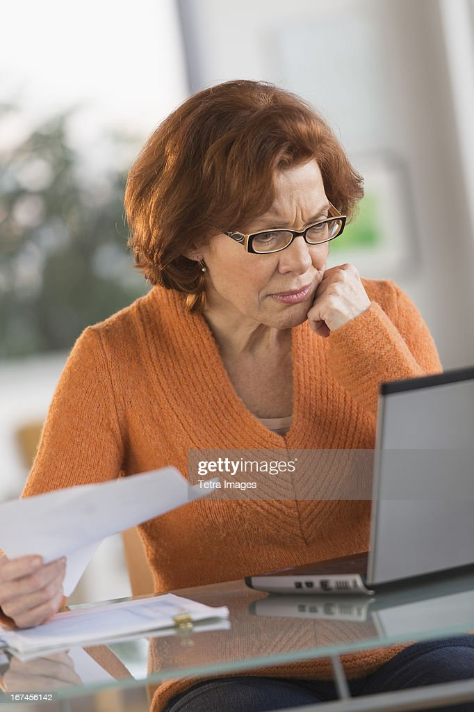 USA, New Jersey, Jersey City, Senior woman working on laptop at home : Stock Photo