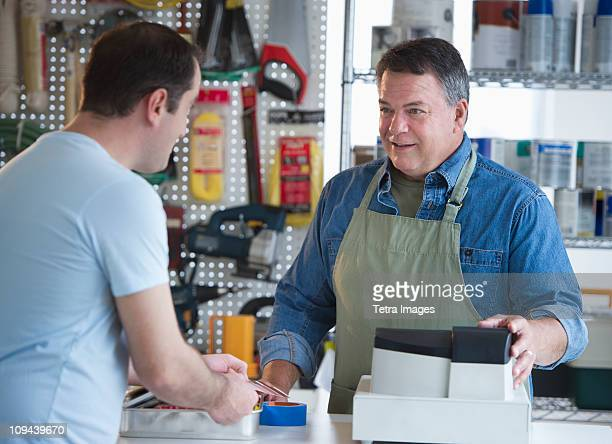 USA, New Jersey, Jersey City, Shop owner serving customer in hardware shop
