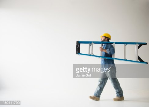 USA, New Jersey, Jersey City, Side view of man carrying ladder