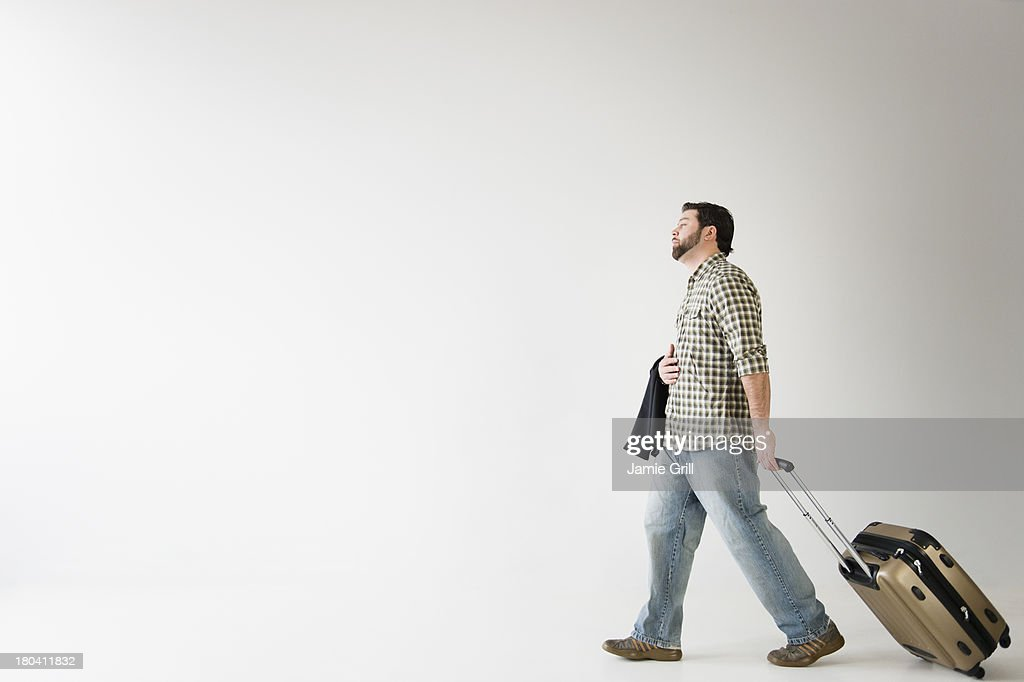 USA, New Jersey, Jersey City, Side view of man walking with suitcase