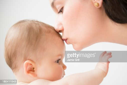 USA, New Jersey, Jersey City, Side view of mother kissing her baby daughter (6-11 months) : ストックフォト