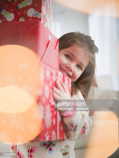 USA, New Jersey, Jersey City, Small girl (4-5 years) carrying Christmas presents