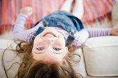 USA, New Jersey, Jersey City, Small girl (4-5 years) lying on sofa