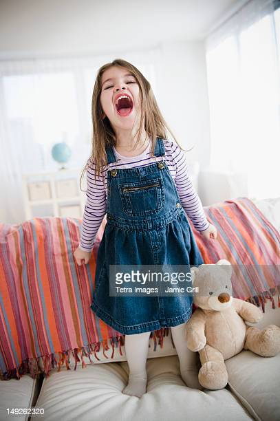 USA, New Jersey, Jersey City, Small girl (4-5 years) standing on sofa