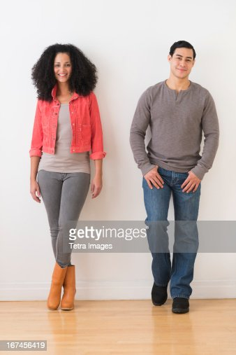 USA, New Jersey, Jersey City, Smiling couple standing against white wall : Stock Photo
