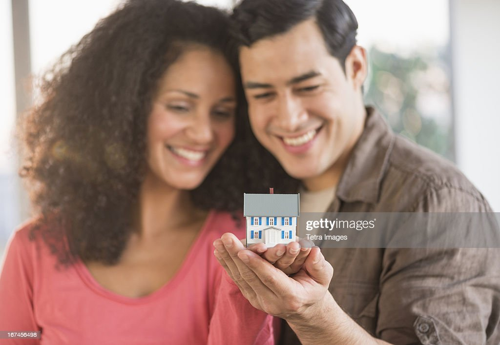 USA, New Jersey, Jersey City, Smiling couple with model home : Stock Photo