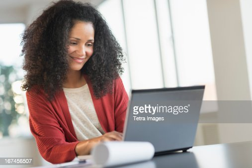 USA, New Jersey, Jersey City, Smiling mid adult woman doing home finances with laptop : Stock Photo
