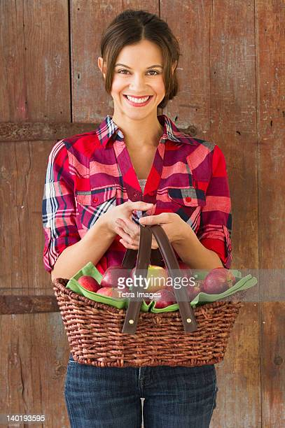 USA, New Jersey, Jersey City, Smiling woman holding basket full of apples