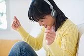 USA, New Jersey, Jersey City, Smiling woman listening music