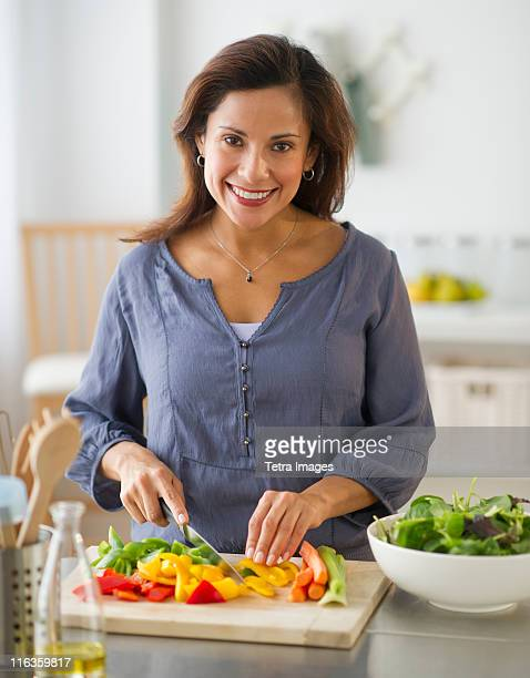 USA, New Jersey, Jersey City, smiling woman preparing food in kitchen