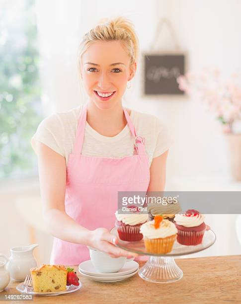 USA, New Jersey, Jersey City, Smiling young woman in apron holding cake stand